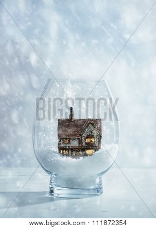 Country cottage decorated with Christmas fairy lights in glass snow globe