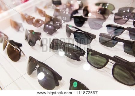 optics, accessory and fashion concept - close up of sunglasses at optician