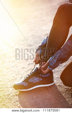 Woman in sportswear tying shoelaces on sneakers outdoor close-up