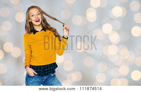 people, style, hairstyle and fashion concept - happy young woman or teen girl in casual clothes holding her hair strand over holidays lights background