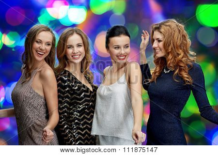 party, holidays, nightlife and people concept - happy young women dancing at night club disco over lights background