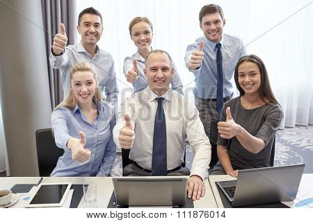 business, people, technology, gesture and teamwork concept - smiling business team with laptop computers showing thumbs up in office