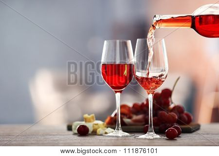 Pouring pink wine from bottle into the wineglass on blurred background