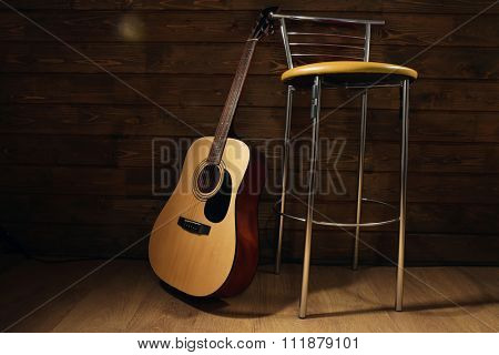 Acoustic guitar propped on wooden wall with bar stool in the room