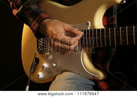 Musician plays electric guitar, close up