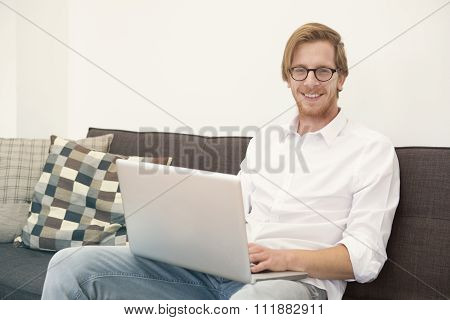 Young Man Sitting On Couch With Laptop And Smiles