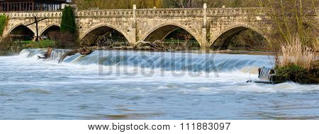 High water flow over Weir near Bath on the River Avon, carrying trees with it