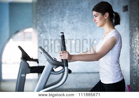 Fitness girl is working out with stepper.Strong brunette with curly hair doing aerobics on stepper