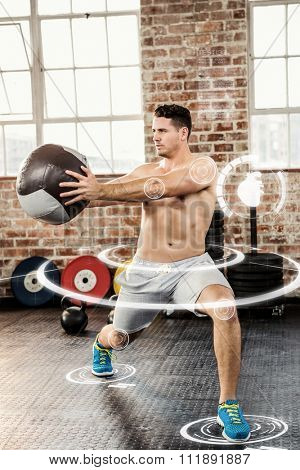 Muscular man exercising with medicine ball against fitness interface