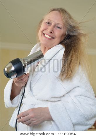 Older woman blow drying her hair