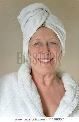 Happy woman with towel wrapped around her head.