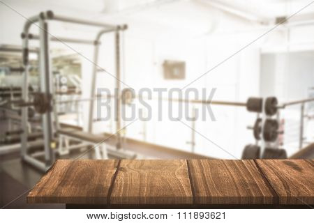 Wooden floor against empty weights room with bench press