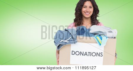 Volunteer holding clothes donation box against green vignette