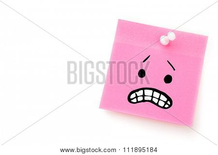 Angry face against pink adhesive note with pushpin