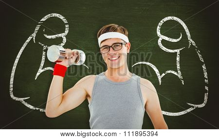Geeky hipster posing in sportswear with dumbbell against green chalkboard