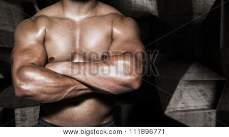 Mid section of a bodybuilder man with arms crossed against black angular design