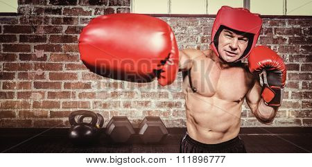 Boxer punching against black background against gym