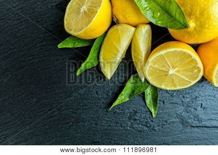 Fresh lemon fruit placed on black stone. Shot from aerial view