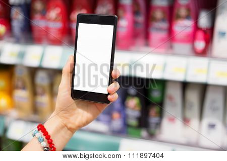 Woman using her smartphone in supermarket