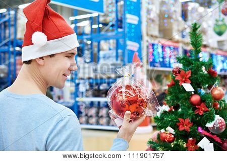 Man In Santa Hat Holding Red Ball Christmas Tree