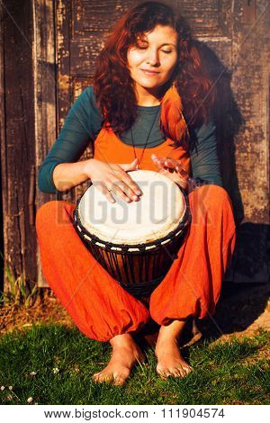 Young barefoot lady drummer playing on her djembe drum on rustic wooden door background