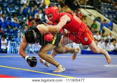 JAKARTA, INDONESIA - NOVEMBER 18, 2015: Ali Abdulkhalikov of Russia (red) fights Ayman Mohamed of Eygpt (black) in the men's 75kg Sanda event at the 13th World Wushu Championship 2015.