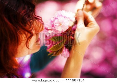 Young woman smelling a beautiful sakura blossom, purple flowers. Spring Magic.