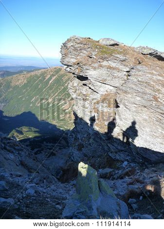 Three Trekkers Shadow Silhouettes At The Rock In Mountains