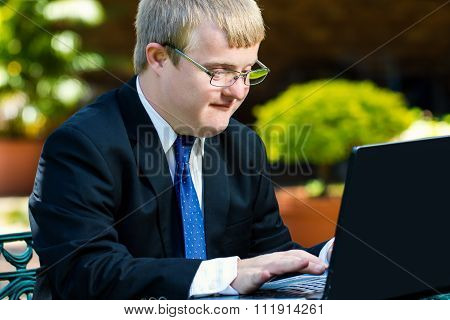 Young Handicapped Businessman Working On Laptop.