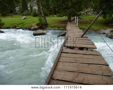 Damaged Wooden Bridge Over A Flooded Stream
