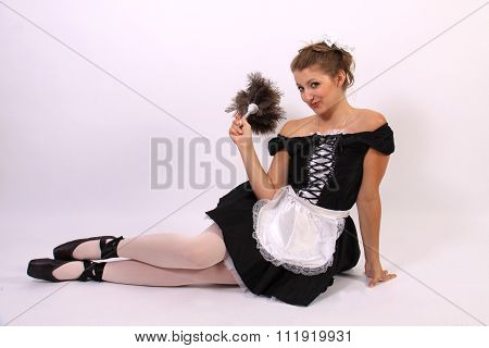 French maid sits on the floor and gives the camera a sassy look