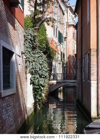 Narrow Canal In Venezia With Houses