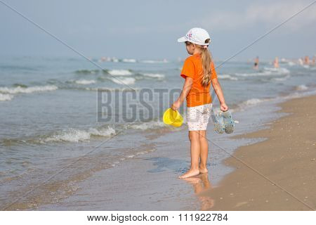 Girl Standing On The Beach With A Bucket And Slaps Hands