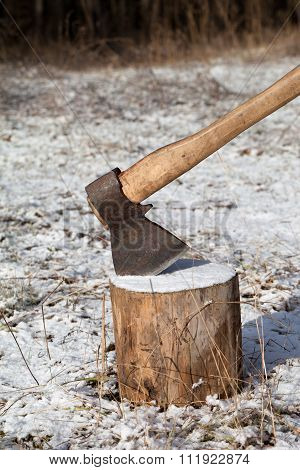 Axe And Log In Winter Forest