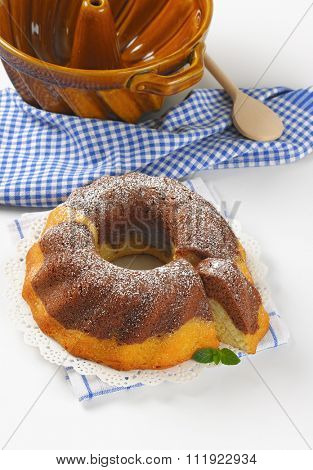 marble bundt cake, bundt cake pan, wooden spoon and checkered dishtowel on white background