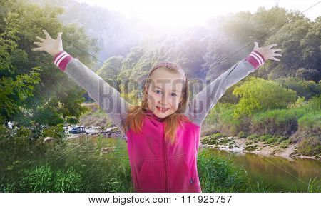 Little girl raising her hands up to the sun. Happy and healthy life concept