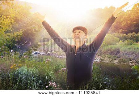 Portrait of elderly good looking woman raised her hands up towards the sun