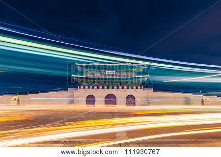 Gwanghwamun Gate Of Gyeongbokgung Palace In Seoul, South Korea With Taillights And Headlights Of Car