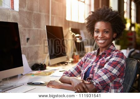 Portrait Of Female Designer Working At Desk In Modern Office