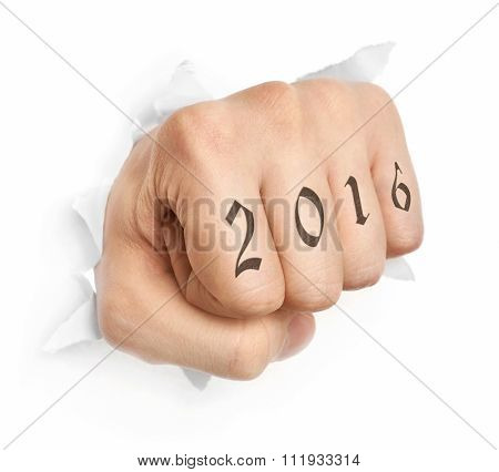 Hand with 2016 tattoo punching through paper isolated on white