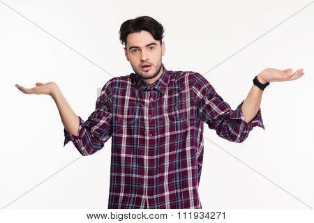 Portrait of a young man shrugging shoulders or holding copyspace on the palms isolated on a white background