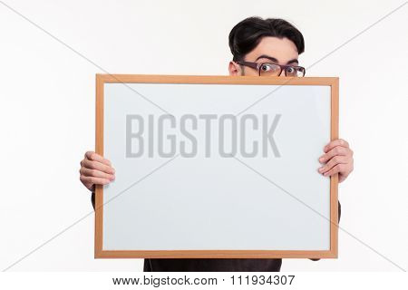 Portrait of a young man peeping from blank board isolated on a white background