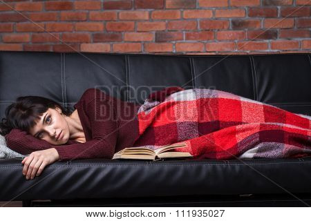 Pensive tired pretty young female lying on sofa covered with plaid coverlet over brick wall background