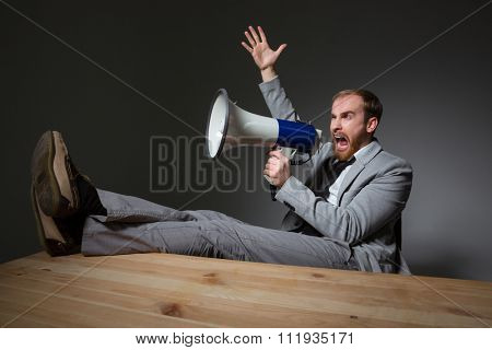 Portrait of a handsome businessman sitting at the table and shouting in megaphone over dark background