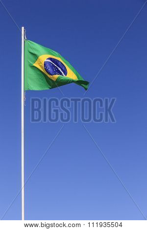 Brazilian flag waving on top of a flagpole in a clear sky day