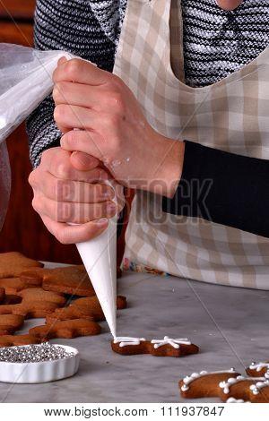 Pastry chef preparing christmas cookies holding a vanilla cream cone.