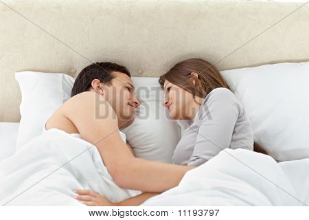 Tranquil Couple Looking At Each Other On Their Bed