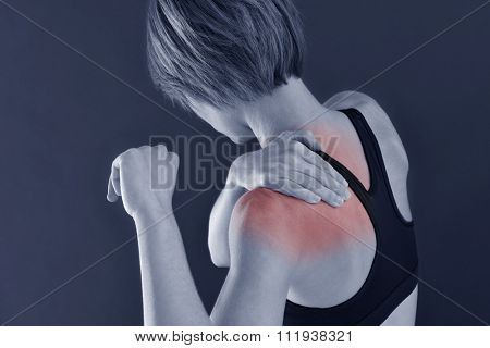 Closeup of fitness girl with shoulder pain, isolated