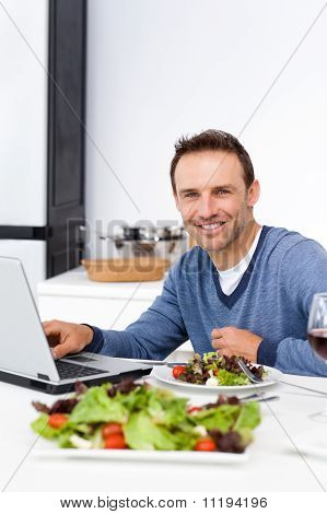 Cheerful Man Working On His Laptop While Having Lunch