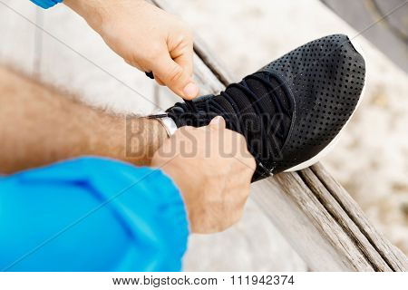 Male runner laces his shoes and prepares to jogging